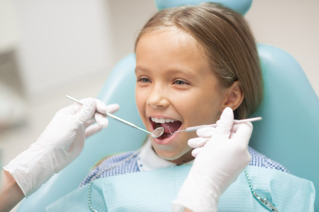 A young dental patient sits in an exam chair while getting a dental checkup