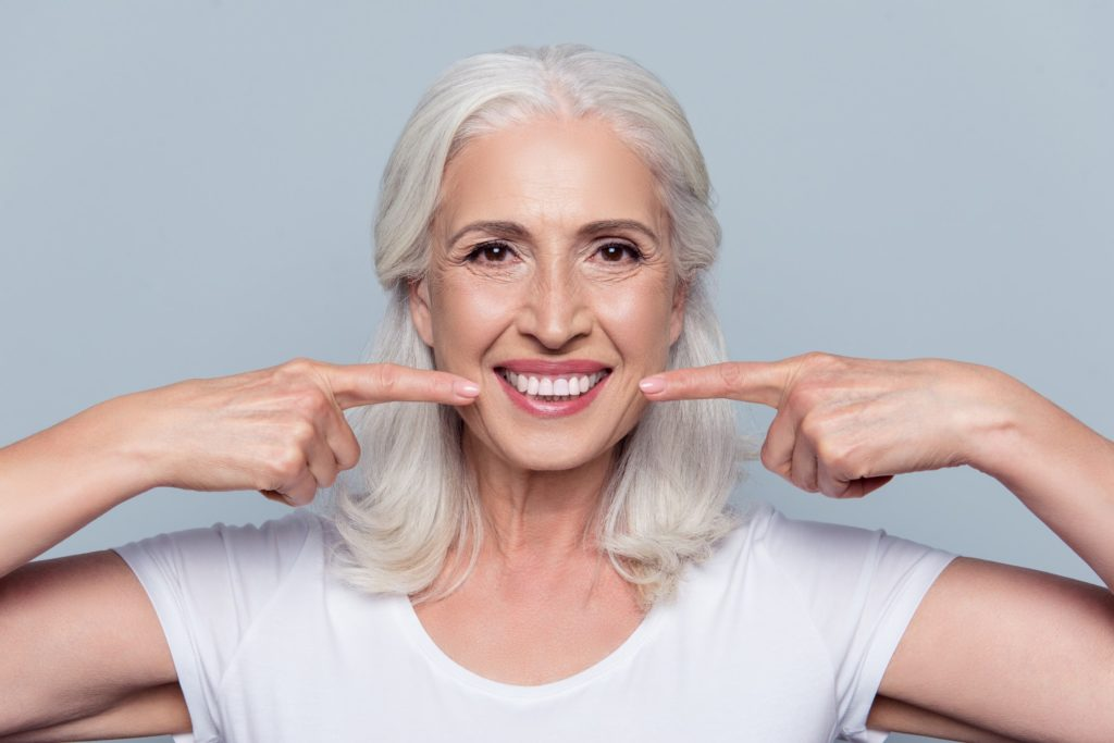 An older woman smiling and pointing to her white teeth with both hands