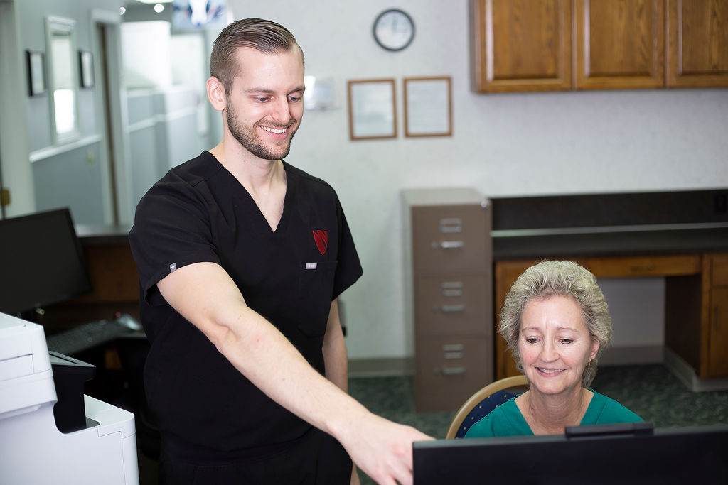 Dr. Fischman and a patient care coordinator discuss patient files in the reception area of Nebraska Dental Center