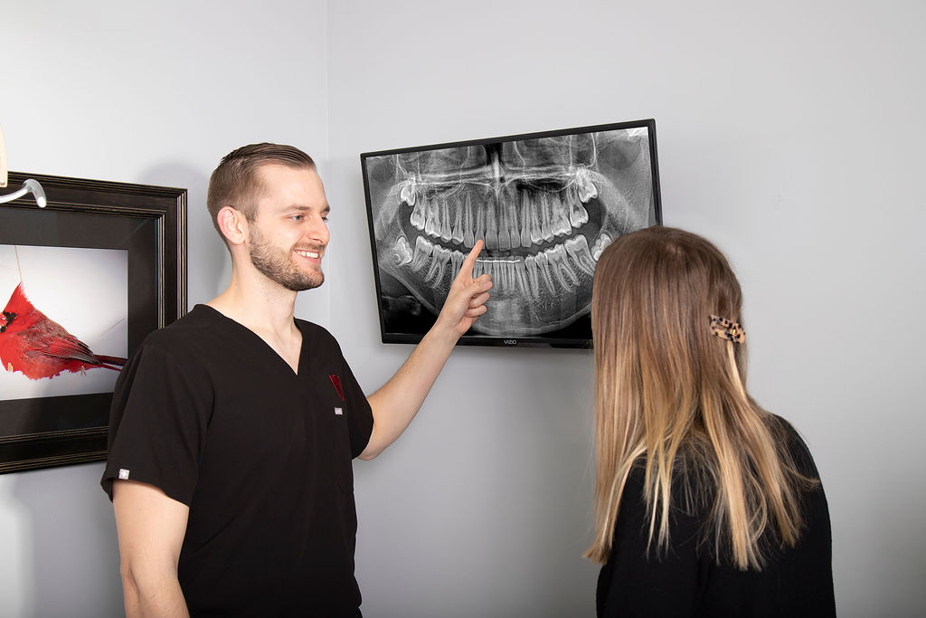 Dr. Fischman points to a dental x-ray on a monitor while speaking to a dental patient